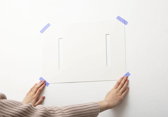 位置決め用の型紙を壁に貼り付け